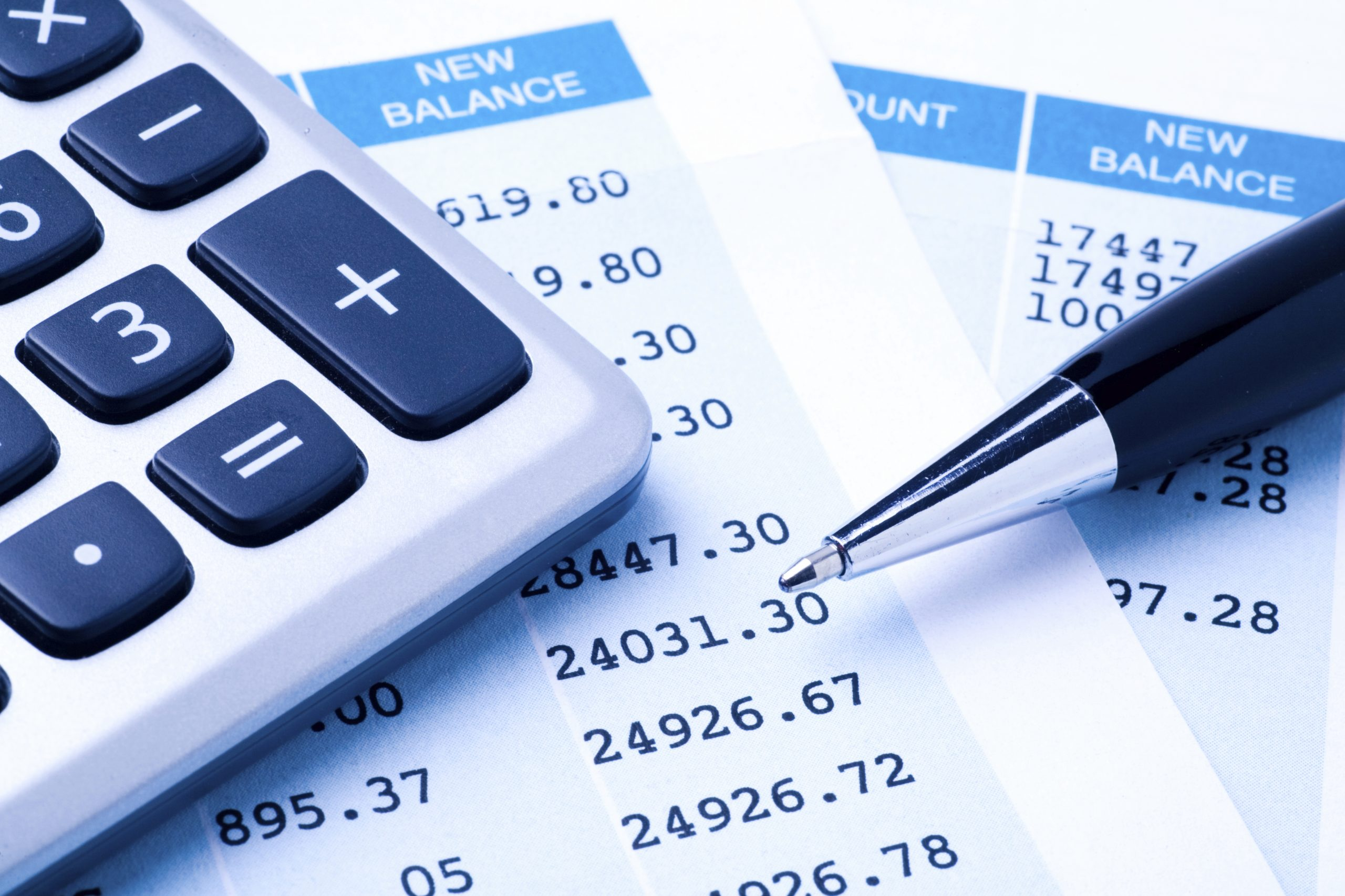 Close-up of a calculator, pen, and financial statement.
